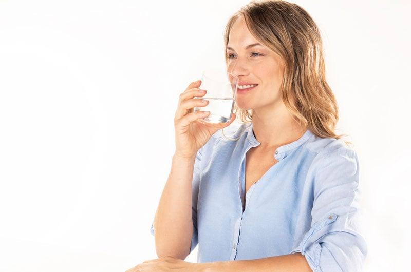 Donna-con-sorriso-che-beve-un-bicchier-dacqua