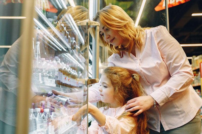 Madre-aiuta-la-figlia-a-prendere-bottiglia-dal-banco-frigo-di-un-supermercato