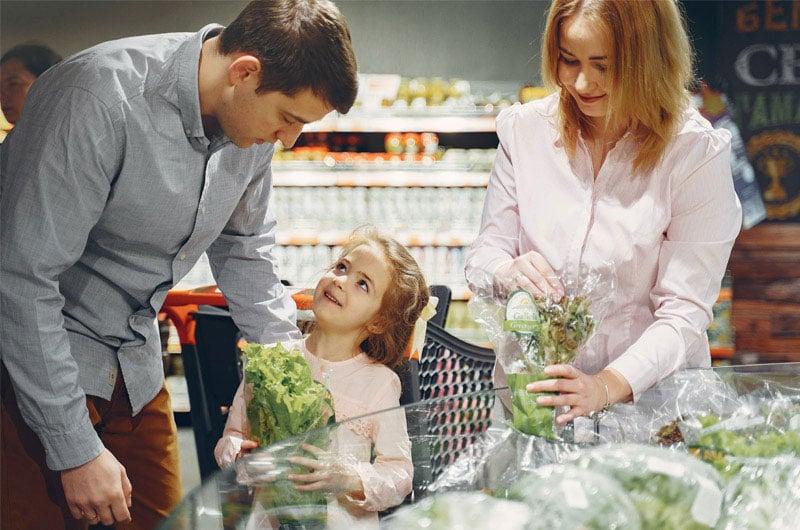 Padre-madre-e-figlia-fanno-la-spesa-comprando-verdure