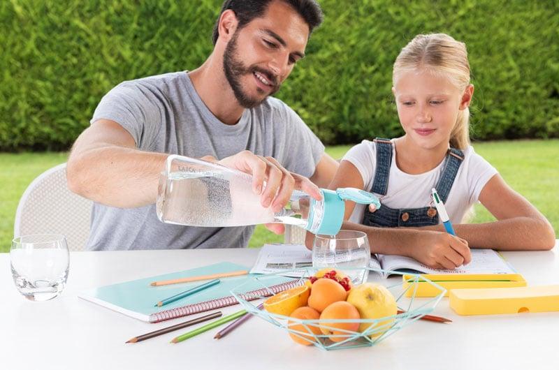 Papà-versa-alla-figlia-un-bicchiere-di-acqua-con-la-bottiglia-filtrante-Flow-n-go-di-Laica