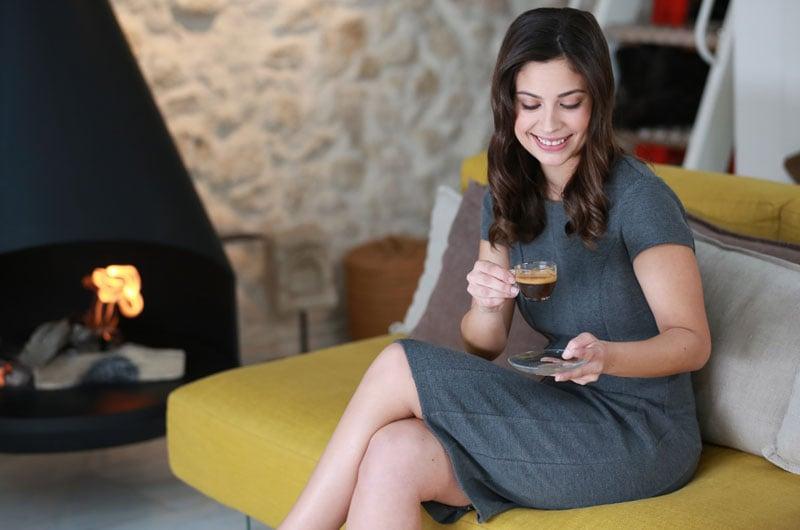 donna-sorridente-che-beve-caffè-su-divano