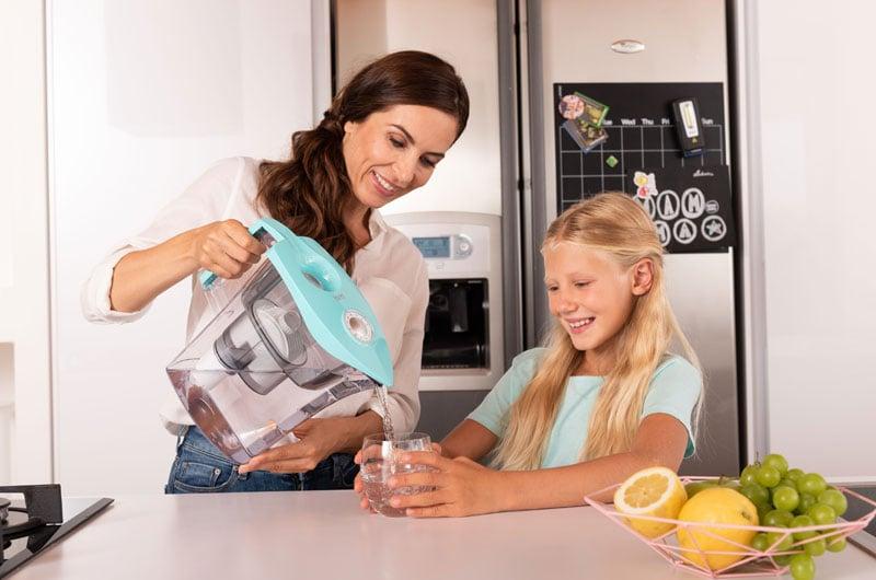 madre-versa-bicchiere-dacqua-alla-figlia-con-caraffa-mikroplastik-stop-microplastiche
